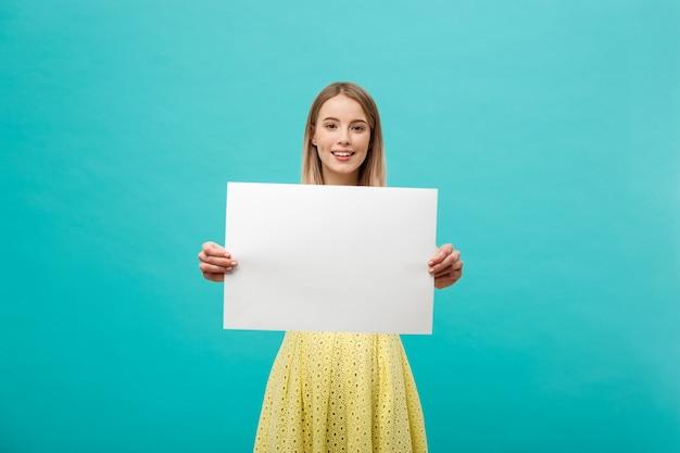 Hermosa niña sonriente y sosteniendo una hoja de papel en blanco, vestida de amarillo