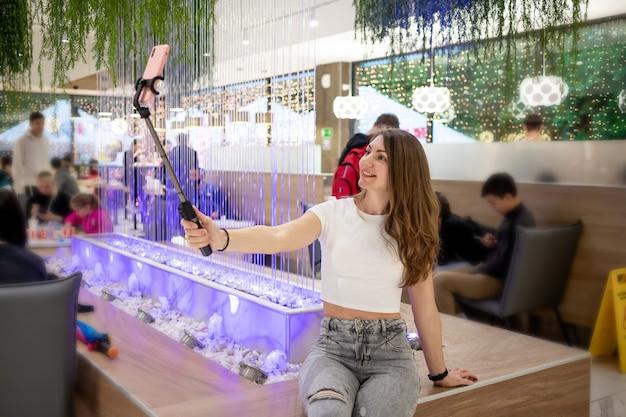 Una hermosa niña sonriente toma un selfie en su teléfono con un palo de selfie en un centro comercial o café en jeans y una camiseta blanca.