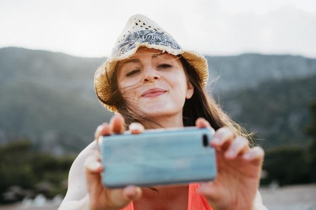Hermosa niña sonriente tomando una foto con su teléfono inteligente al atardecer sobre la montaña
