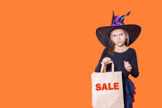 Una hermosa niña sonriente con un vestido negro y un sombrero de bruja sostiene una bolsa de papel artesanal con las palabras venta sobre un fondo naranja. concepto de compras de halloween