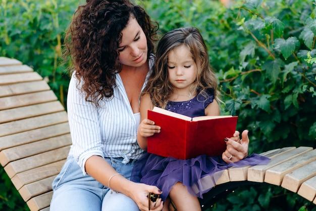 Hermosa niña sosteniendo un libro, su madre ayuda a la niña a leer, al aire libre