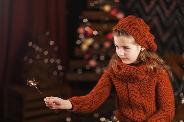Hermosa niña sosteniendo luces de bengala ardientes.