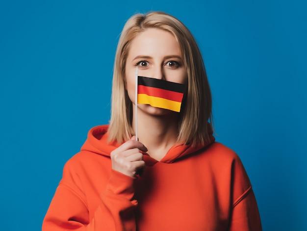 Hermosa niña sostiene la bandera de alemania en la mano