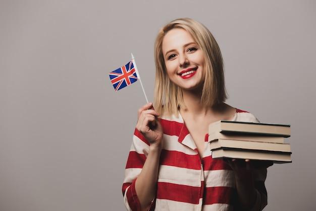 Hermosa niña sostiene la bandera británica y libros