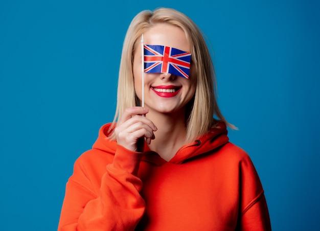 Hermosa niña sostiene la bandera británica en la mano