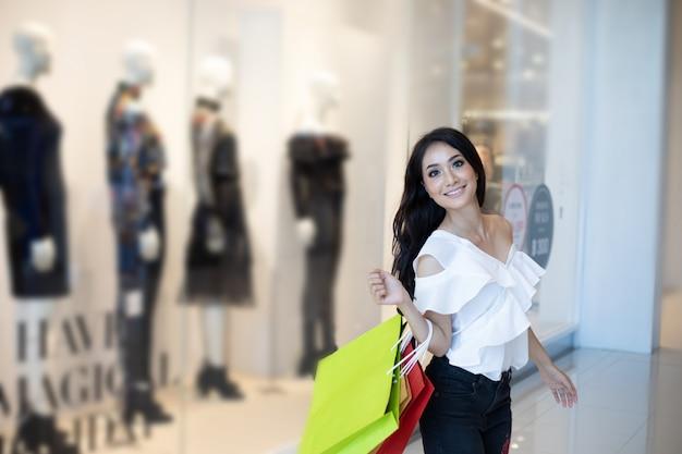 Hermosa niña sostiene bolsas de compras y sonríe mientras hace compras en el supermercado / centro comercial