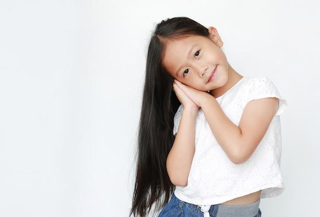 Hermosa niña sueño gesto posando con las manos juntas mientras sonríe