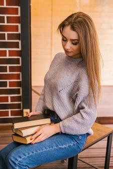 Una hermosa niña con un suéter de punto gris lee un libro en un acogedor café, el concepto de agradable ocio y comunicación. estudiante o empresaria.