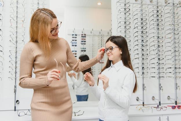 Hermosa niña en la tienda de óptica junto con mamá elige gafas nuevas
