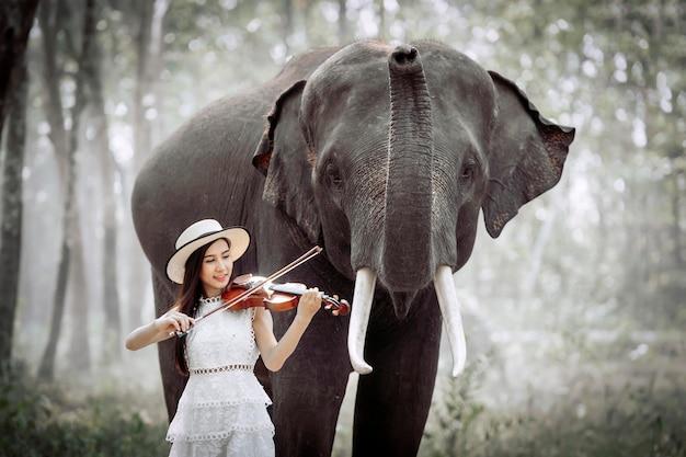 La hermosa niña toca el violín para que el elefante la escuche.