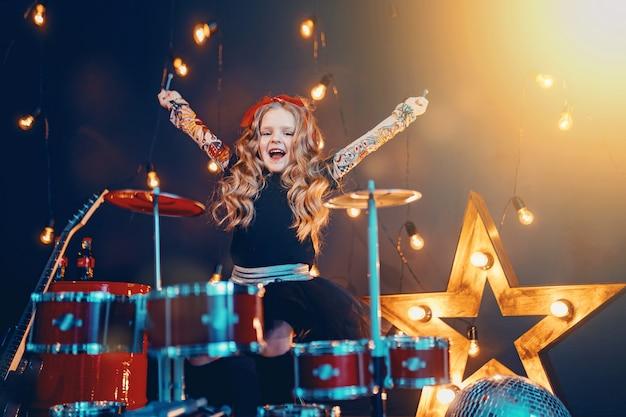 Hermosa niña tocando la batería