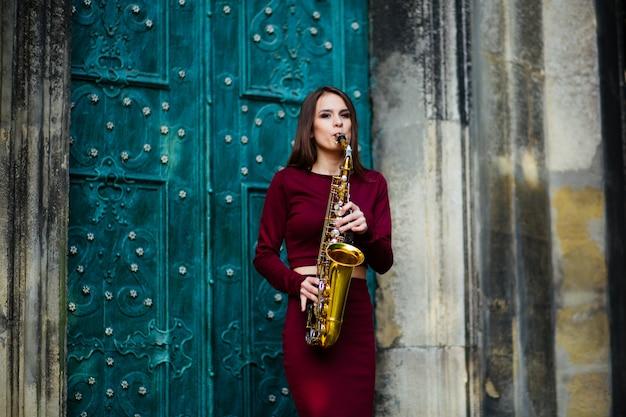 Hermosa niña tocando el saxofón