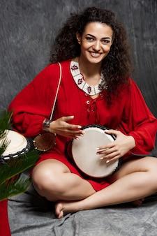 Hermosa niña tocando el tambor en plantas tropicales sobre gris