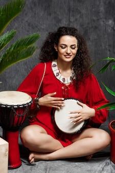 Hermosa niña tocando el tambor en plantas tropicales sobre pared gris