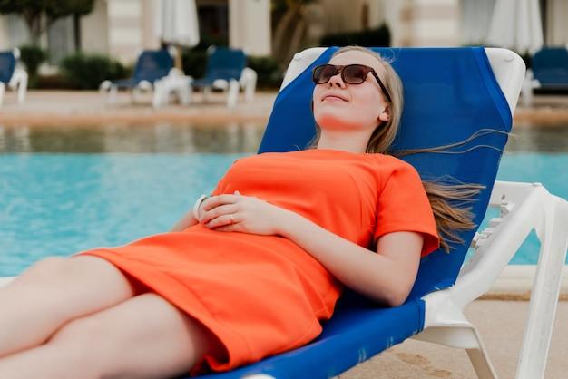 Una hermosa niña en traje de baño y gafas se encuentra y descansa sobre una tumbona en el patio de una villa en bali.