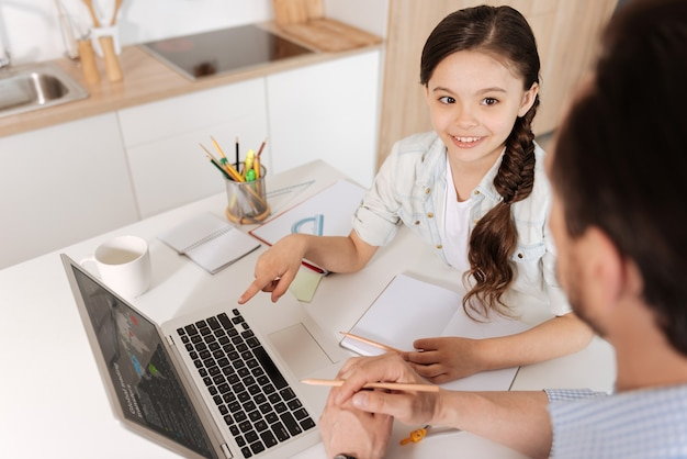 Hermosa niña con una trenza de cola de pez sentada en la encimera de la cocina llena de papelería y apuntando a la computadora portátil mientras mira a su padre