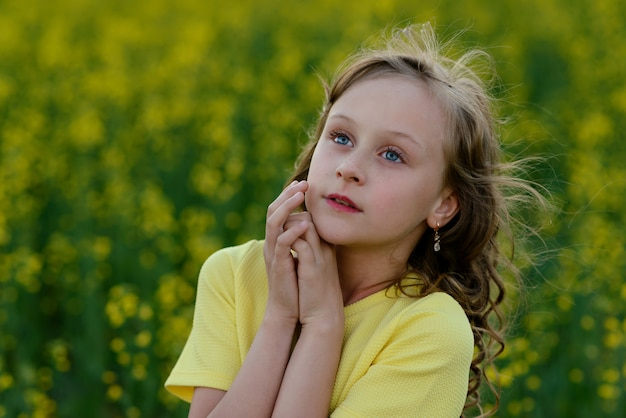 La hermosa niña en un vestido amarillo en el campo floreciente