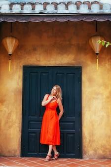 Una hermosa niña con un vestido rojo está de pie contra la puerta oscura de una vieja casa amarilla con linternas chinas. arquitectura de la antigua ciudad de hoi an. vietnam.