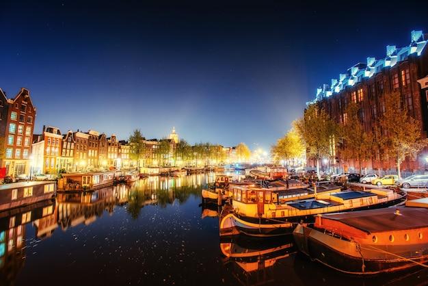 Hermosa noche en amsterdam. iluminación de edificios y