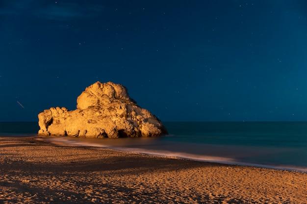Hermosa noche a la orilla del mar con roca