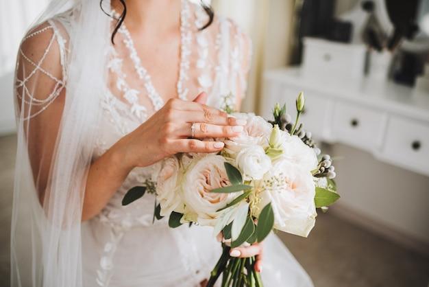 Hermosa novia caucásica joven sosteniendo su ramo de novia