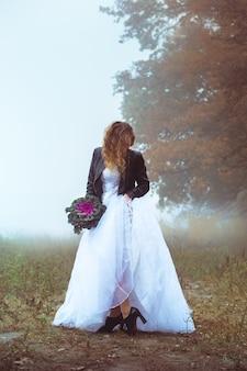 Hermosa novia y una chaqueta de cuero con un ramo sobre un fondo de un campo brumoso
