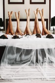 Hermosa novia y damas de honor mostrando sexy piernas en la cama