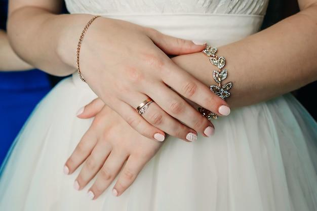 Hermosa novia dobla las manos con el anillo en el vestido de novia