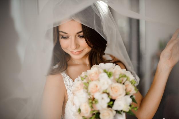 Hermosa novia con elegante maquillaje en vestido blanco
