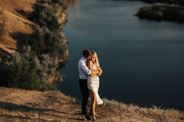 Hermosa novia feliz y el novio abrazándose en el lago. hermosa joven novios de novio y novia de pie en la colina