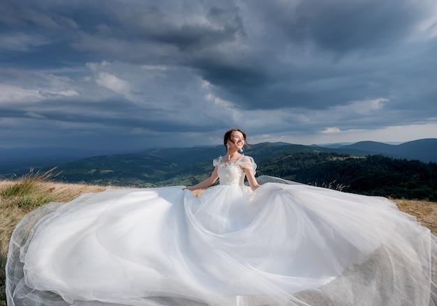 Hermosa novia feliz vestida con un vestido de novia de lujo en el día soleado en las montañas con el cielo nublado