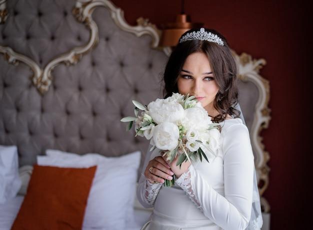 Hermosa novia en la habitación del hotel con ramo de novia hecho de eustomas y peonías blancas