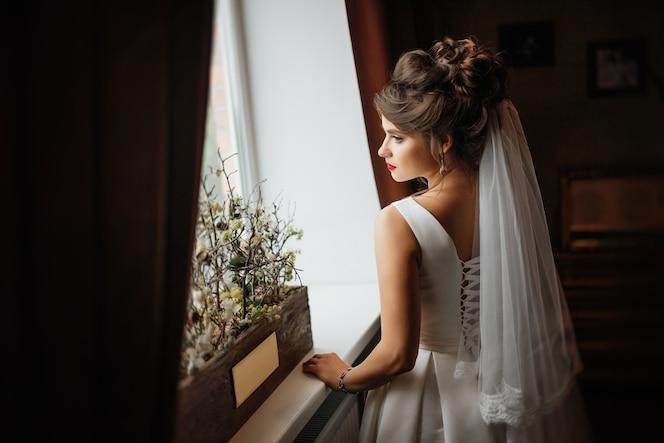Hermosa novia joven de pie cerca de la ventana en el interior oscuro, su mano en el alféizar de la ventana