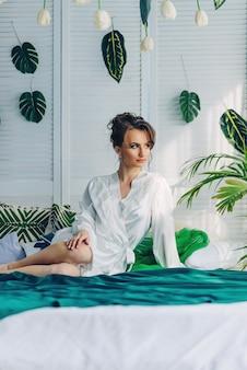 Hermosa novia joven sentada en una cama cubierta con una manta verde en una habitación con flores