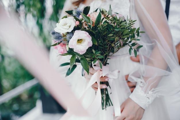 Hermosa novia en un largo vestido de novia blanco