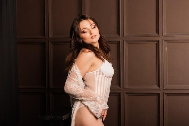 Hermosa novia en lencería blanca sentada en su dormitorio y estudio