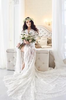 Hermosa novia en lencería y con una corona de flores en la cabeza, en la mañana antes de la boda. bata blanca de la novia, preparándose para la ceremonia de la boda. sexy chica en el cama