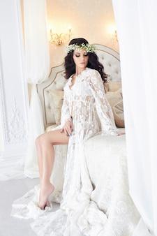 Hermosa novia en lenceria y con guirnalda de flores.