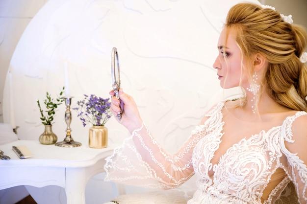 Hermosa novia se mira en el espejo