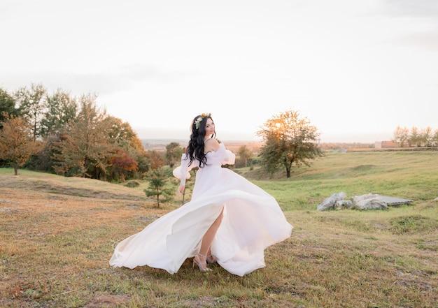 Hermosa novia morena caucásica está bailando en el prado amarillento en la cálida noche de otoño
