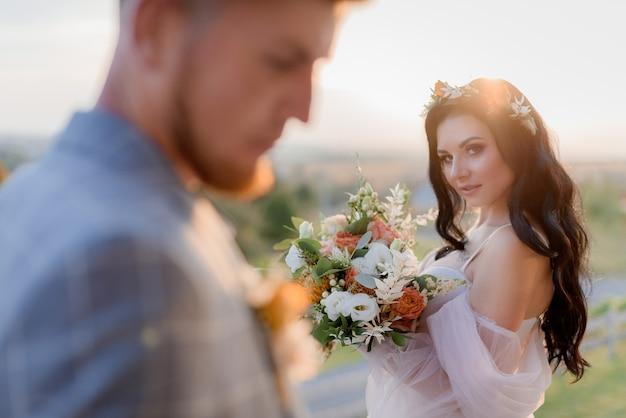 Hermosa novia morena con mirada astuta está sosteniendo un bonito ramo de novia hecho de eustomas frescas y vegetación en la puesta de sol y el novio borroso