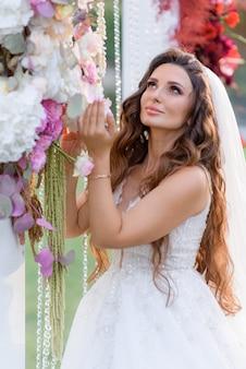 Hermosa novia morena de pelo largo vestida con un vestido de novia cerca del arco de la boda floral