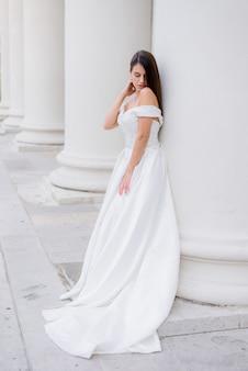 Hermosa novia morena está de pie cerca de la enorme columna blanca
