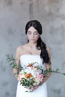 Hermosa novia mujer en vestido de novia con un ramo de flores
