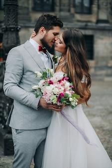 Hermosa novia y el novio abrazándose y besándose en el día de su boda al aire libre