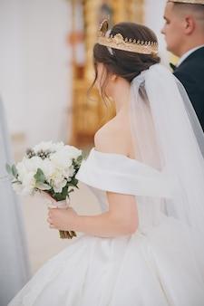 Hermosa novia y el novio en coronas de oro. ceremonia de boda tradicional recién casados en la antigua iglesia de fondo.