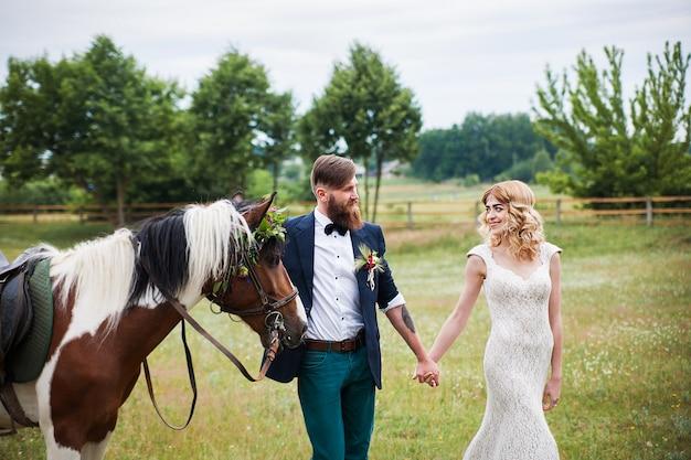 Hermosa novia y el novio están caminando con un caballo, estilo rústico