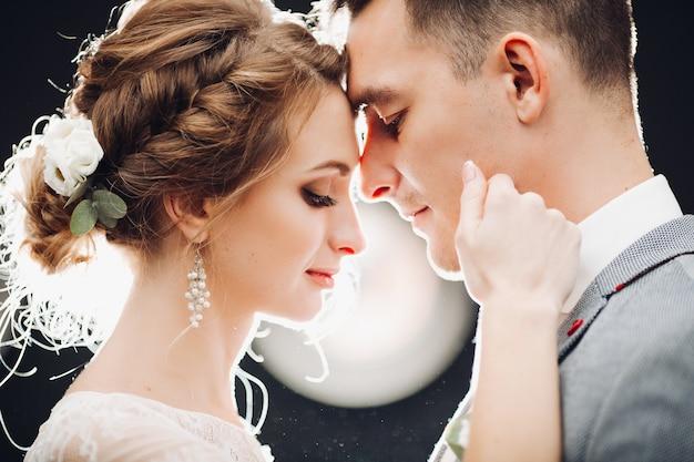 Hermosa novia y novio guapo tocando por caras entre sí