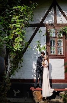 Hermosa novia y el novio de pie cerca uno del otro en la casa antigua, hermosa pareja, día de la boda, retrato.