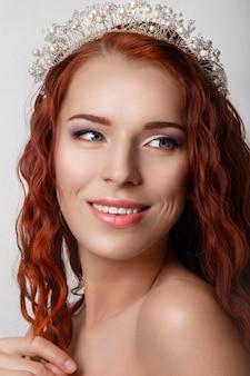 Hermosa novia con el pelo largo y rizado rojo.